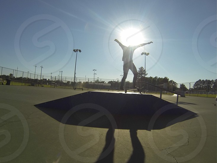 A skateboard rider performing a trick at sunset photo