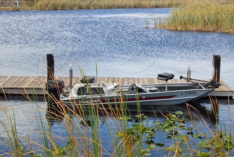 Small rowboat is docked near a wooden pier behind reeds in a calm lake photo