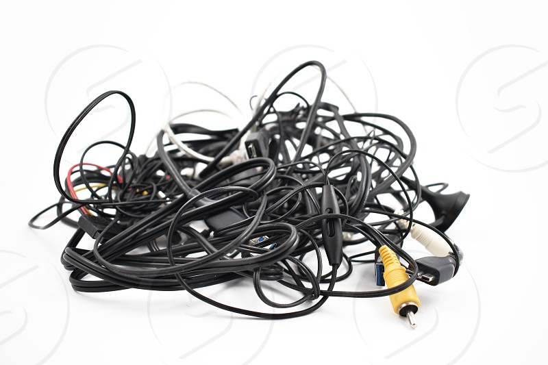 Tangled cables and connectors. Tangle of cables on a white background. Plastic electronic waste. Pile of cables and connectors photo