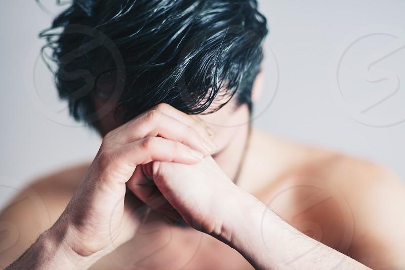 Young man in pain praying photo