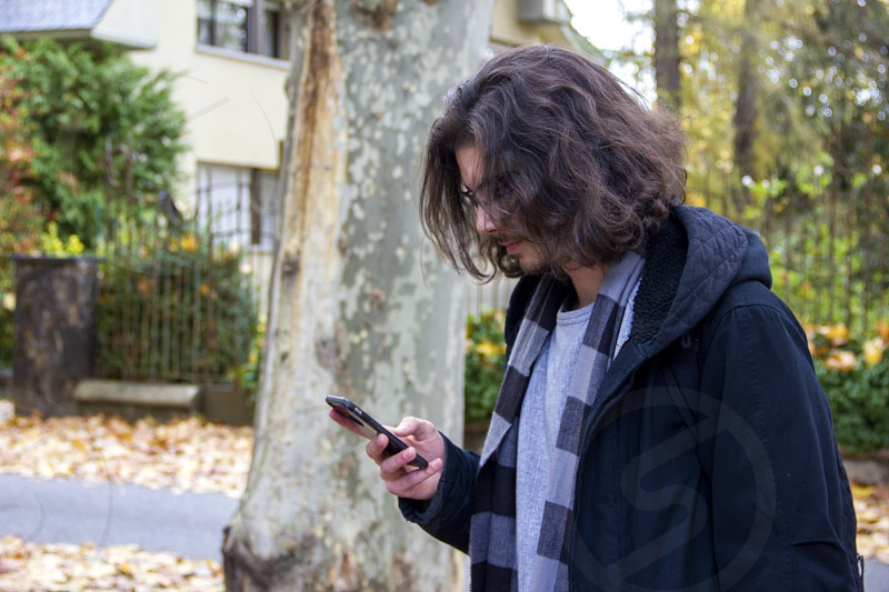 A young man with long curly hair in warm clothes walks down the street and writes a message on the phone. photo
