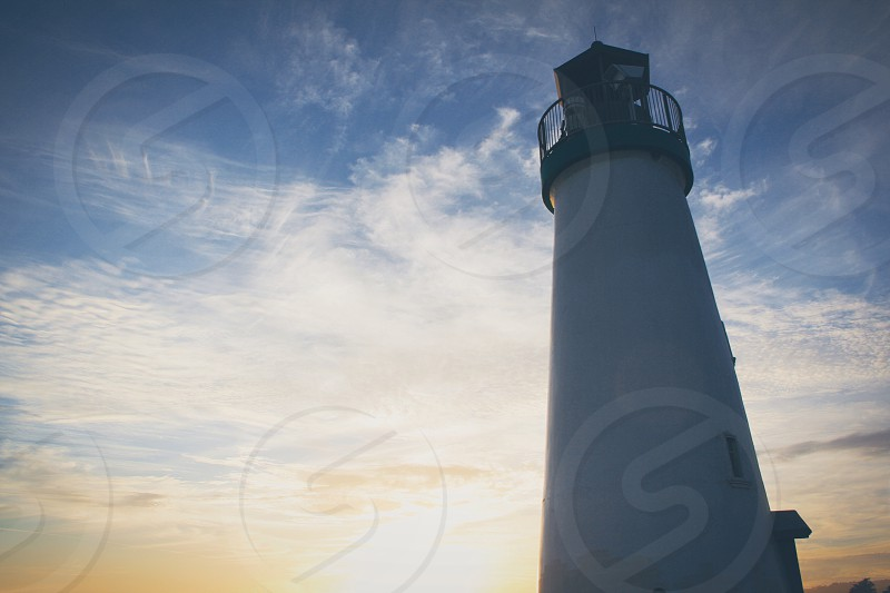 low angle photo of white lighthouse under blue sky background photo