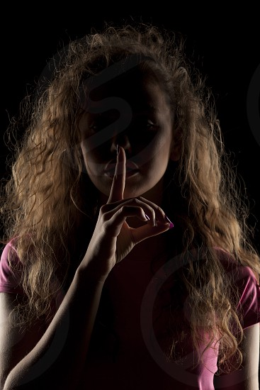 unknown woman with the face in the shadow holding finger on her lips photo