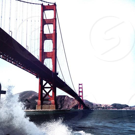 view of golden gate bridge from ocean level against white sky photo