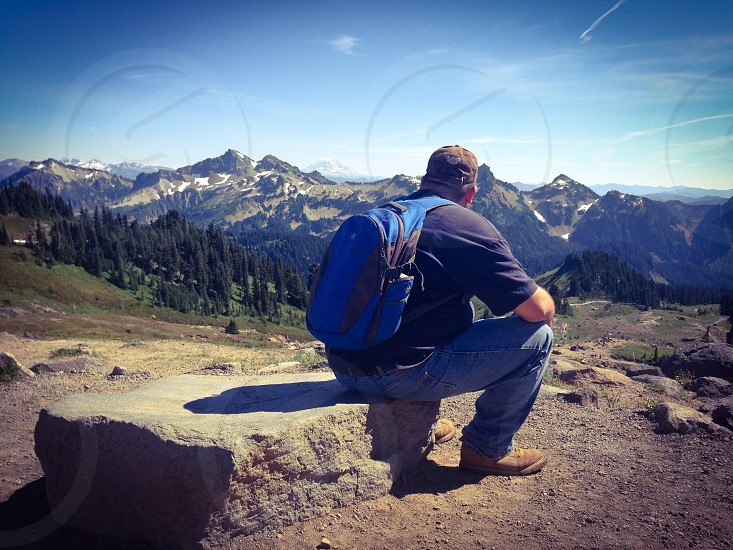 man with blue backpack sitting on a rock overlooking mountains photo