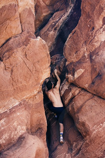 man wearing black athletic shorts rock climbing photo