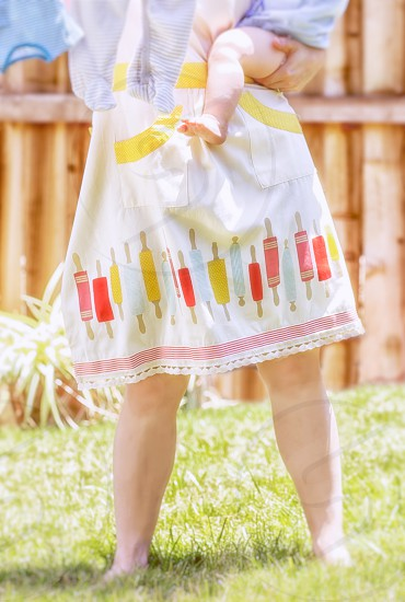Unidentifiable woman hanging laundry in yard holding baby.  Springtime colors.  Bright light.  Retro apron. photo