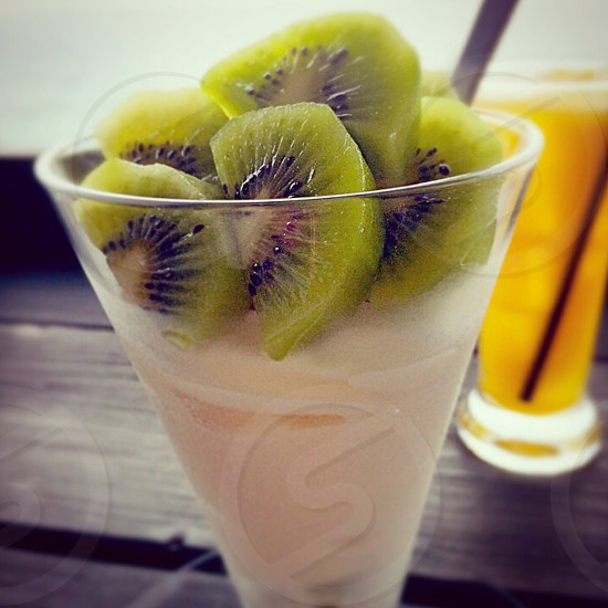 slice kiwi on clear drinking glass photo