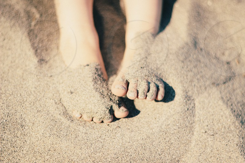 barefooted child on brown sand during daytime photo