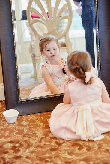 Flower girl wedding day bridal suite getting ready admiring sweet girl pretty on pink mirror photo