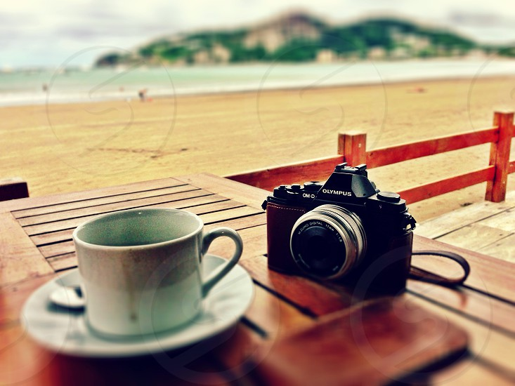canon camera on outdoor table by white coffee cup on saucer photo