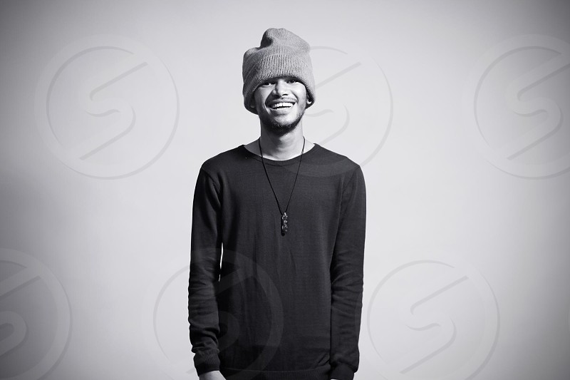 grayscale photo of man wearing long sleeve shirt knit cap and string pendant necklace photo