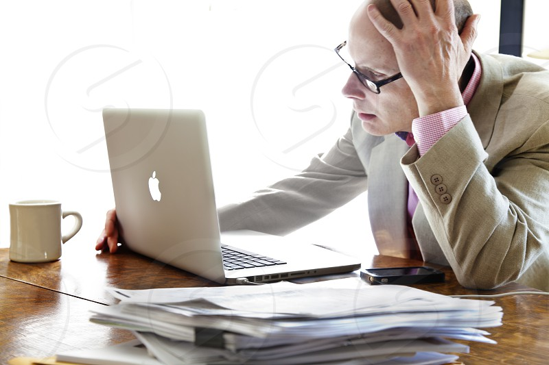 man in beige suit using silver Apple Macbook Pro photo