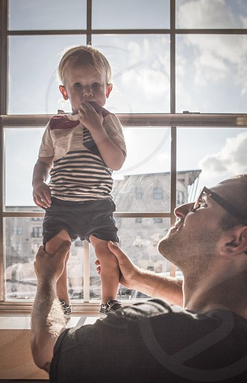 A father holds his son up in a window. photo