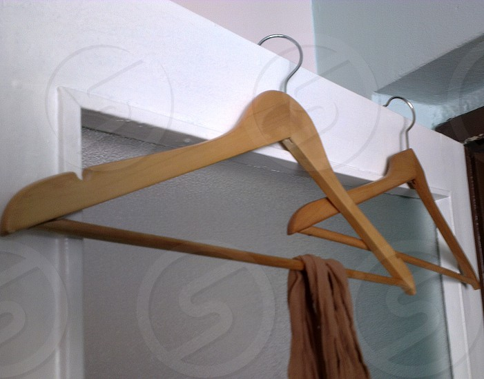 two brown wooden clothes hangers photo