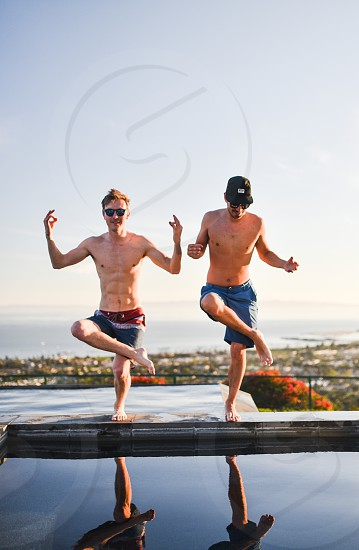 2 topless men standing on pool side under clear sky photo