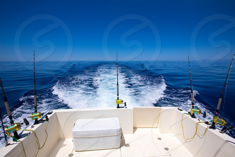 Fishing boat stern deck with trolling fishing rods and reels in blue ocean sea photo