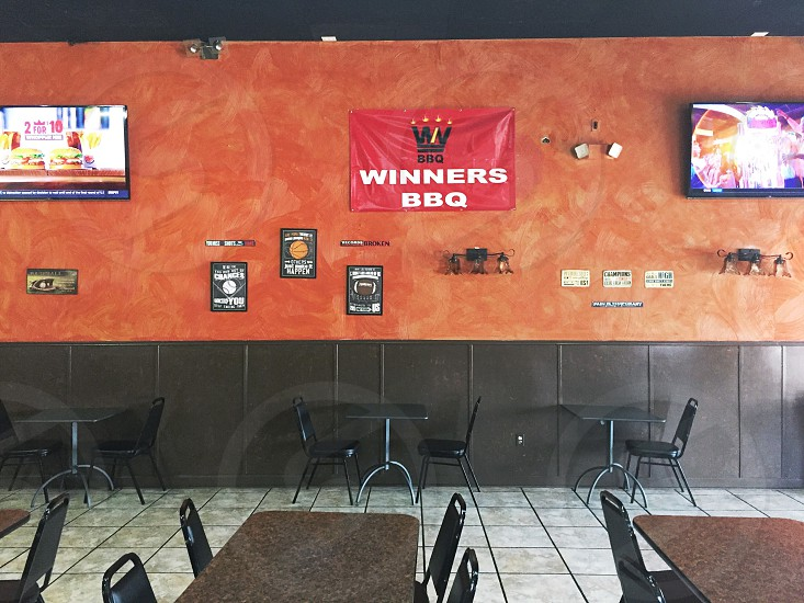 winners bbq flag on a wooden wall between 2 flat screen wall mounted tv above dinette set photo