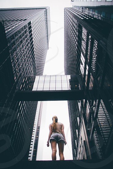 woman with long blonde hair standing in between 2 tall buildings interconnected photo