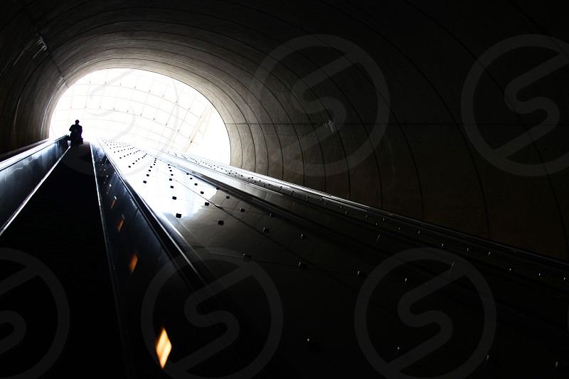 An individual commuter makes their way up/down an escalator.  Travel move steep long large tunnel contrast dark bright oval architecture. photo