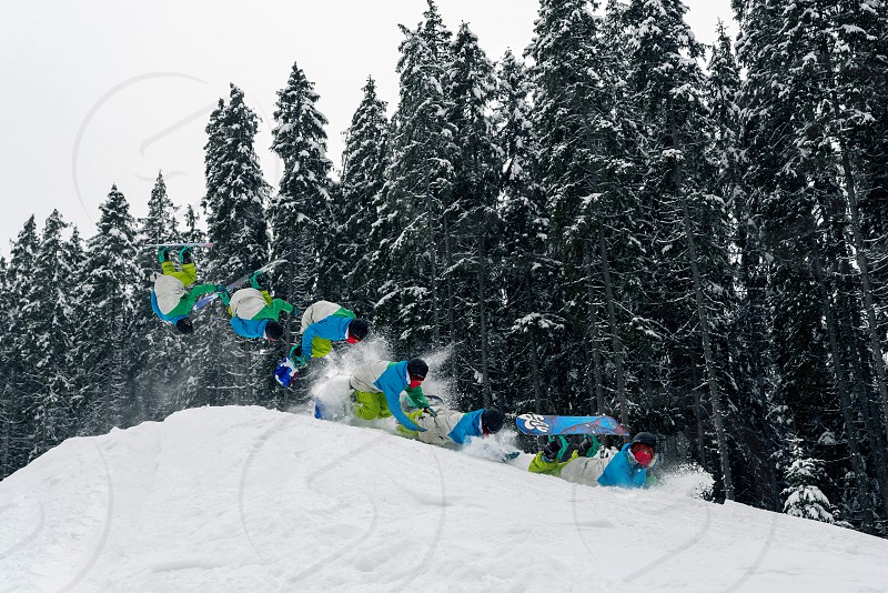 a snowboarder makes a flip in the snowpark on a springboard photo
