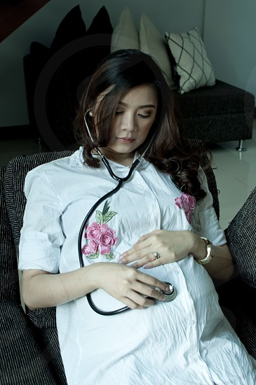 A pregnant woman is examining her belly with an stethoscope photo
