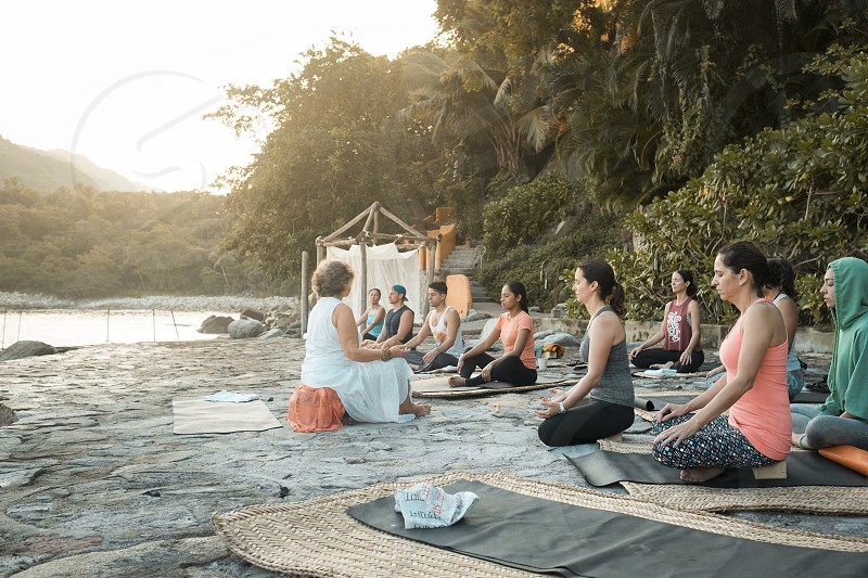 Yoga retreat Puerto Vallarta - Mismaloya Mexico - multiple people sitting on yoga mats meditating with eyes closed. photo