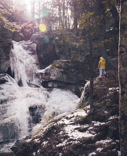 person in yellow hoodie on rock formation facing waterfalls in forest photo