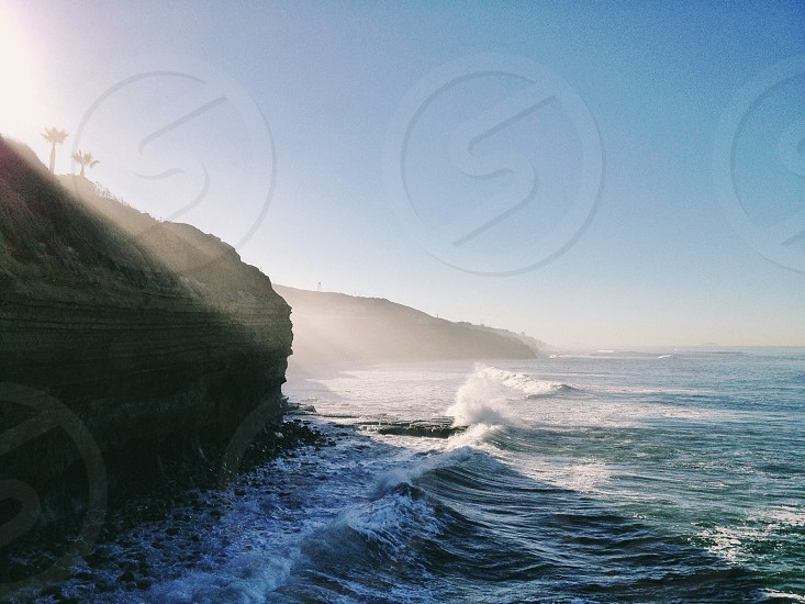 rock formation with white beach waves photo