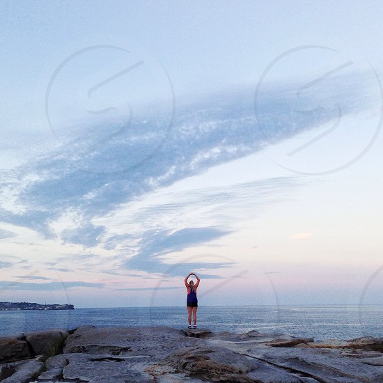 woman standing on beach cliff photo