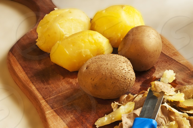 peeled potatoes on a kitchen board photo