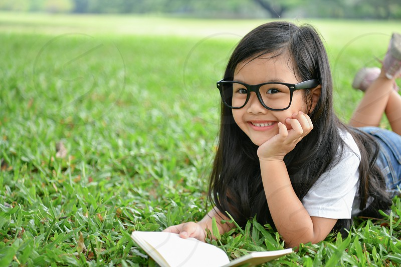 Education Concepts. The girl is reading a book in the garden. Beautiful girl is seriously studying. Beautiful girls are happy learning. photo