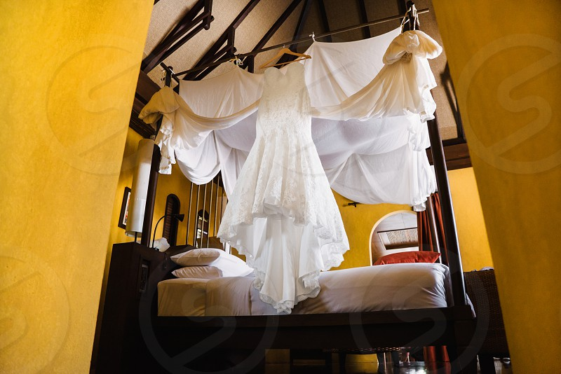 Wedding dress of the bride hanging on the bed photo