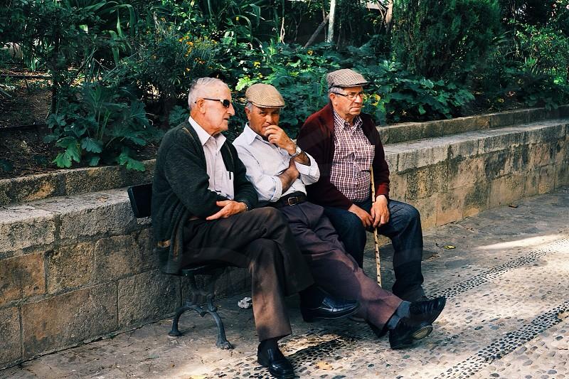 3 men sitting on park bench photo