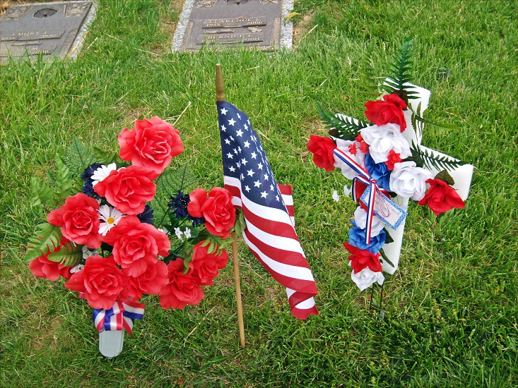 floral arrangement and flag on grave photo