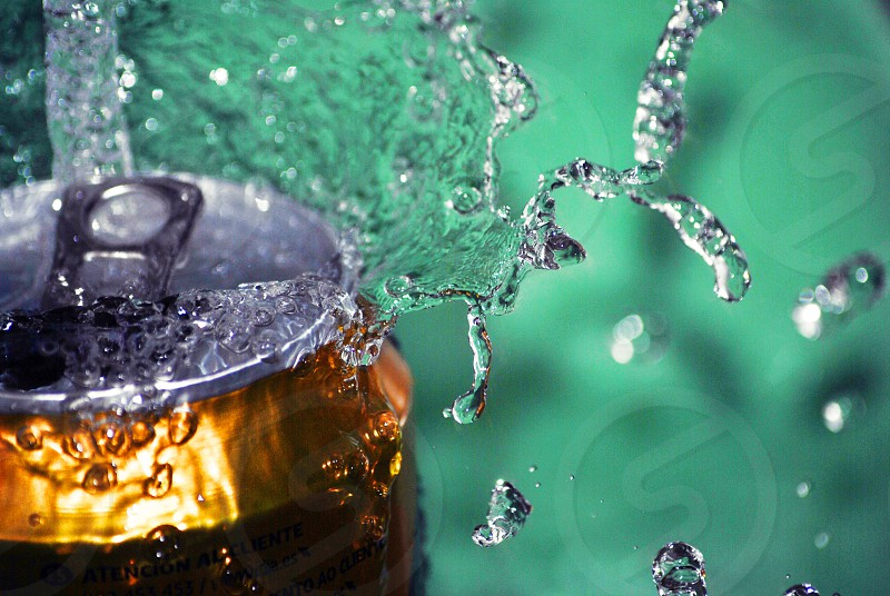 gold and gray soda can with water splash focus photography photo