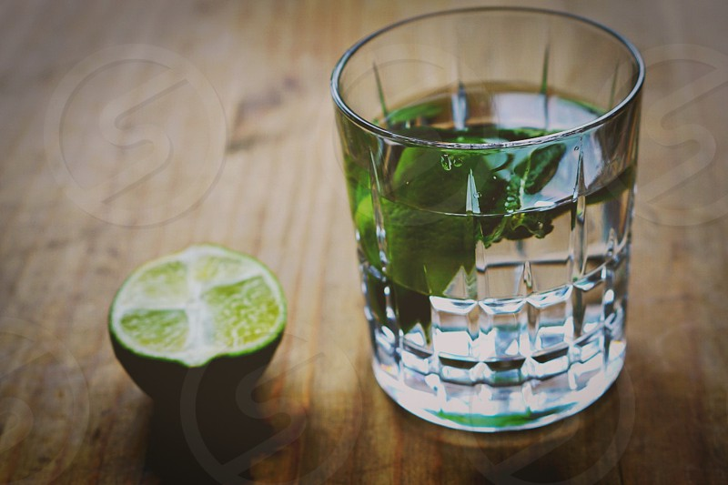 sliced lime beside clear shot glass with liquor and green leaf on brown wooden table photo