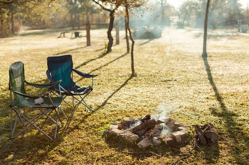 Two chairs sit around a campfire in the morning photo