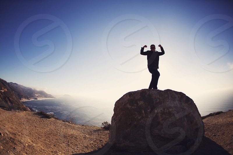 man in black button up long sleeved shirt standing on gray rock photography photo