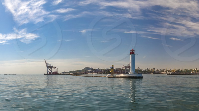 Lighthouse at the entrance to the harbor of the Odessa port the sea gates of Ukraine in a sunny summer day photo