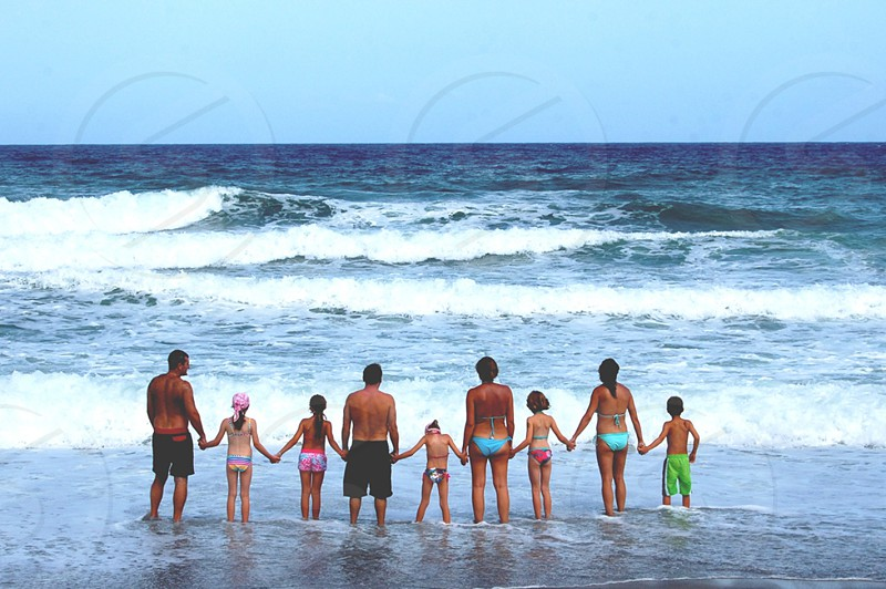 A large family with children and adults holding hands are on the seashore looking at the horizon in Mojacar Andalusia Spain photo