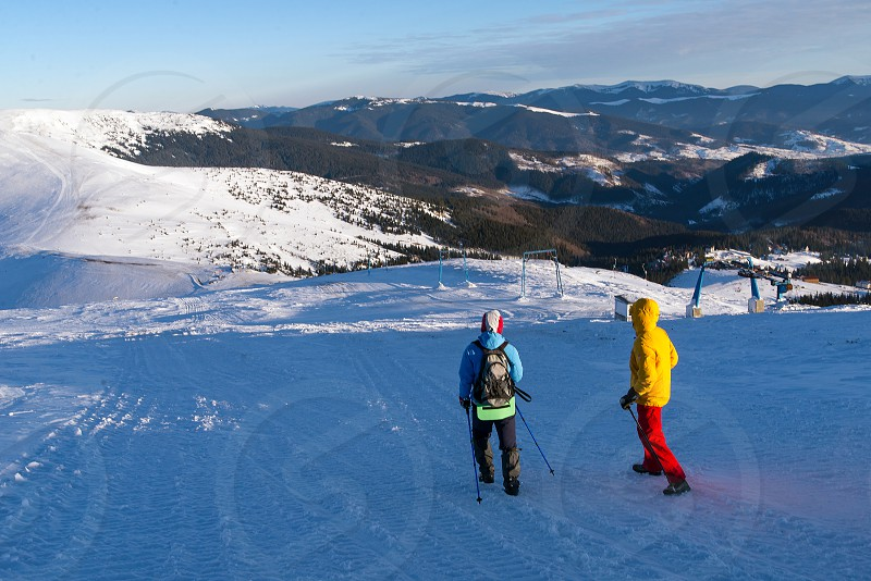 two tourists hiking in winter snowy mountains photo