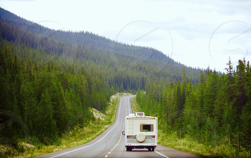 white van speeding on road surrounded by trees overlooking hill under cloudy sky during daytime photo