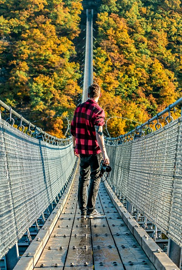 man in black and red checked sport shirt and gray denim jeans stands in gray metal bridge photo