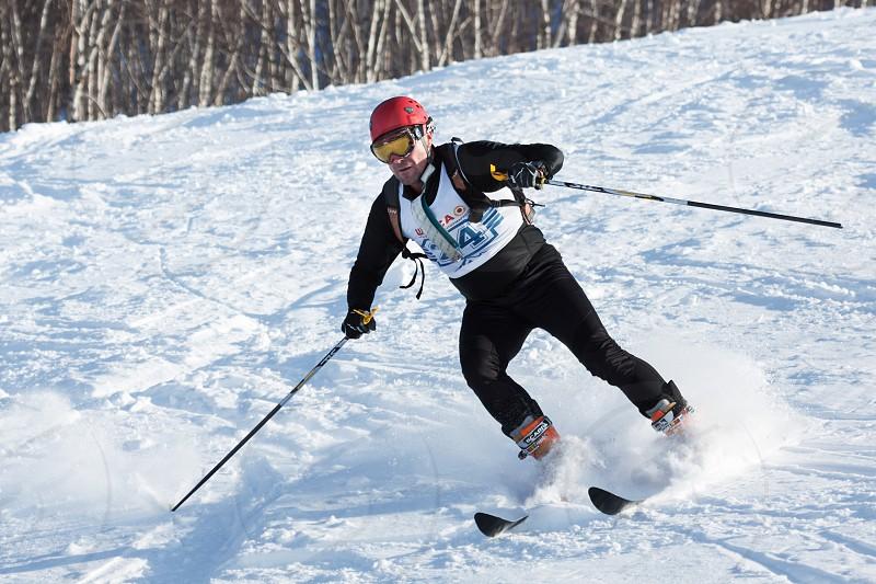 KRASNAYA SOPKA PETROPAVLOVSK-KAMCHATSKY KAMCHATKA RUSSIA - FEB 4 2012: Ski mountaineer rides skiing on mountain. Ski-mountaineering competitions - Cup Petropavlovsk-Kamchatsky City. photo