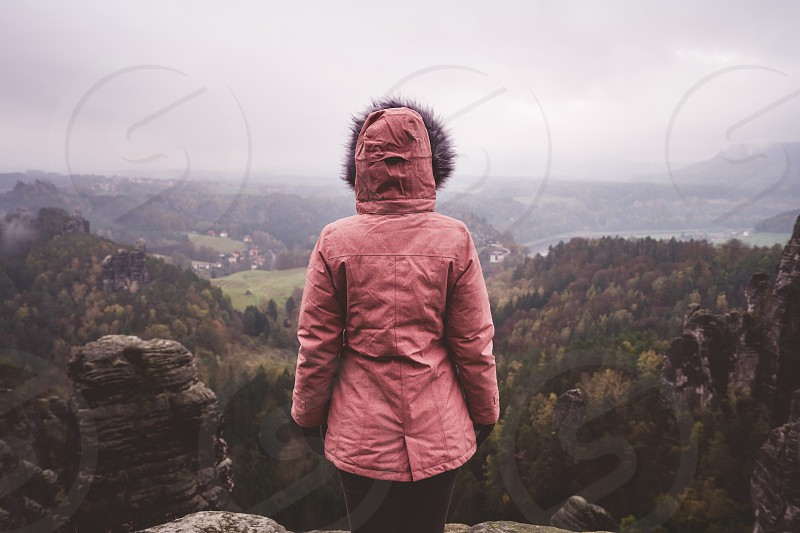 Young woman in outdoor clothing standing alone on mountain top with wild forest in the valley in background. Travel lifestyle harmony concept. Rear view. photo