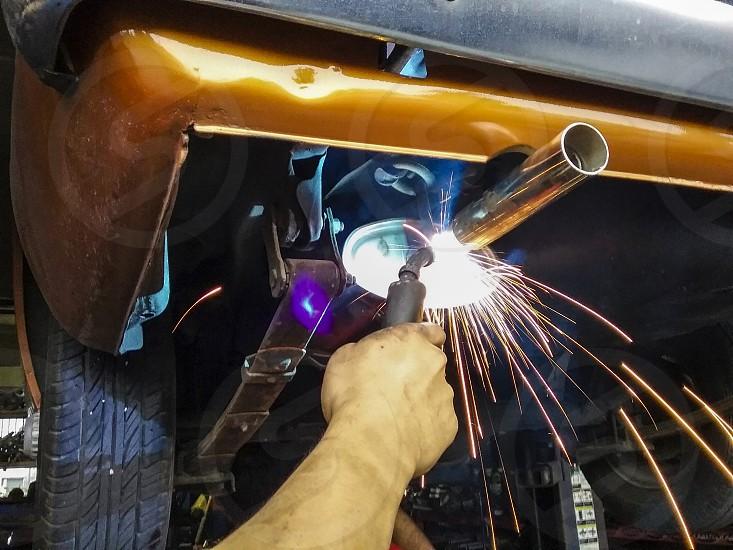 Closeup of blue collar worker welding classic car muffler photo