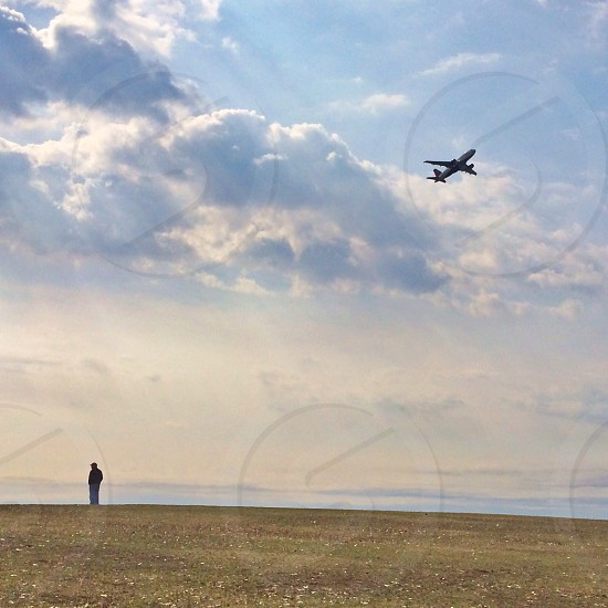 man standing on ground with airplane passing by in the sky photo