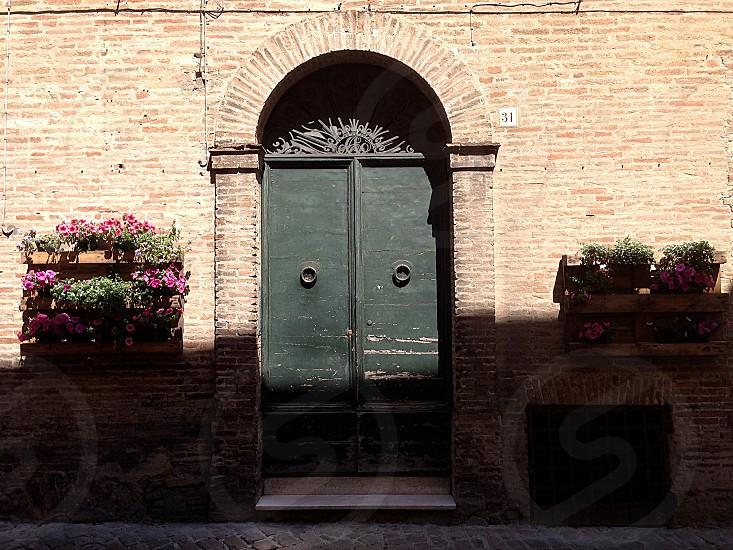brick building double black doors flower boxes photo