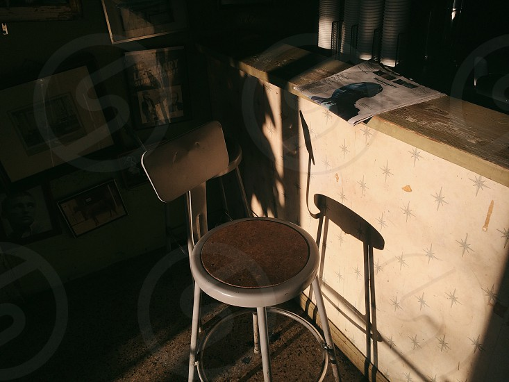 chair in front of counter with newspaper on it photo